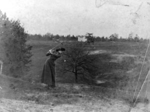 """Looking north-east from Morningside Avenue near Durie Street, Muriel Dick is seen here enjoying golf. The white houses in the background are on the west side of Beresford Avenue between Bloor and DeForest. Nine hole golf course was built by the Epiphany Anglican Church. Swansea was the first small community in York County to have a golf links. The club house """"Herne Hill Cottage"""" was on the East side of Ellis Avenue. Photo via Toronto Library."""