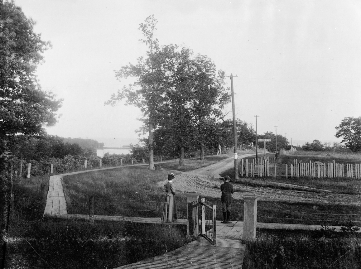 "The front gate of Morningside Church looking south down Ellis Avenue. The street sign reads ""College Street Extension"" and the one on the tree reads ""Ellis Avenue"". Adam Smith, son of R. C. Smith, and Miss Ada Smith, daughter of Wm. Smith (no relationship) are looking down towards the lake. Grenadier Pond can be seen past the board sidewalk."